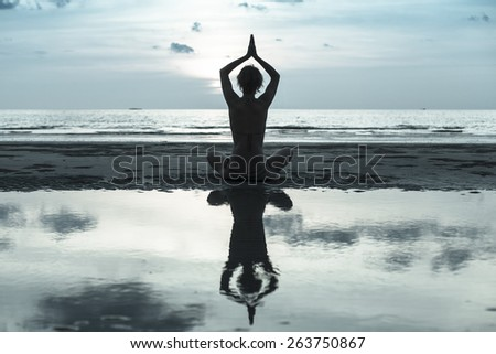 Silhouette young woman practicing yoga on the beach, image in cold colors. - stock photo
