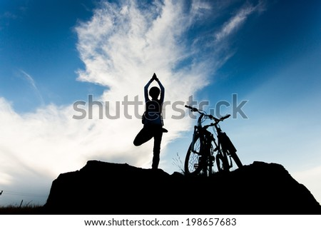 Silhouette young woman practicing yoga, relaxing after riding bikes high in mountain over cloudy sky background - stock photo