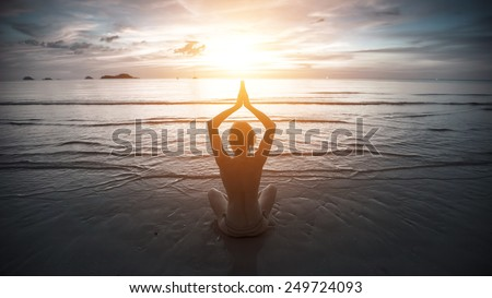 Silhouette young yoga woman on the beach at sunset in cold colors. - stock photo