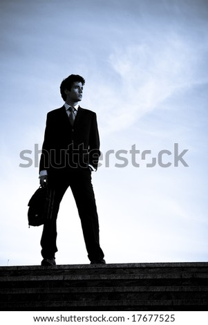Silhouetted businessman posing on stairs against blue sky. - stock photo