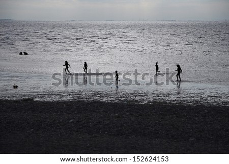 Silhouetted children - boys and girls - playing in the sea at sundown - stock photo
