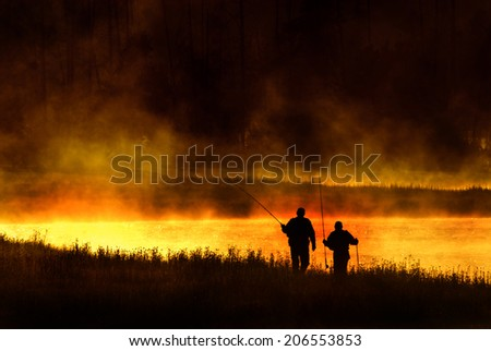 Silhouetted fly fishermen walking on bank of Madison River in Yellowstone National Park - stock photo