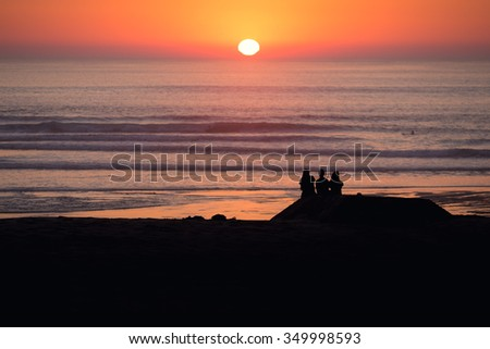 silhouetted friends sitting on bunker at the Atlantic coast watching the sunset - stock photo