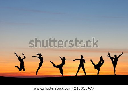 silhouetted group tumbling and dancing in sunset  - stock photo