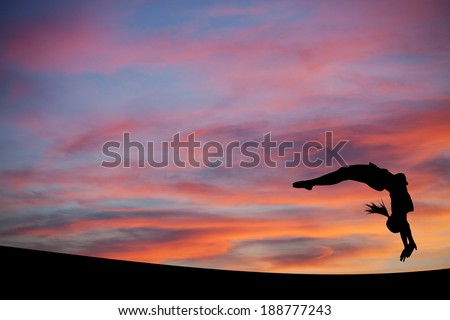 silhouetted gymnast doing a back handspring in sunset sky  - stock photo