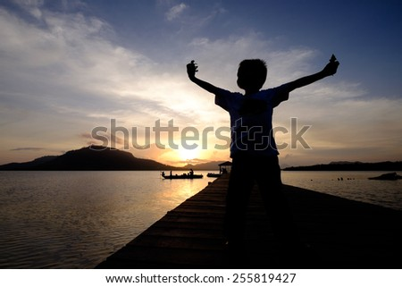 Silhouetted happy kid (boy) spreading his arms joyously while holding his toys in both hand  with a beautiful sunset moment - stock photo