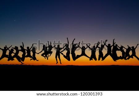silhouetted large group of teens jumping after sunset - stock photo