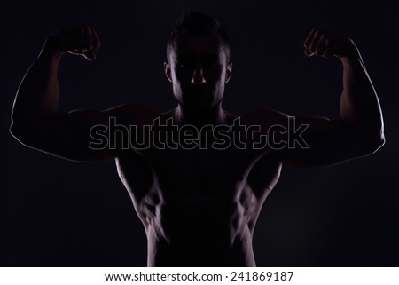 Silhouetted muscular man showing his biceps - stock photo