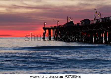 Silhouetted pier with orange and red sunset in the distance - stock photo