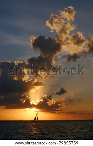 Silhouetted sailboat at sunset in Biscayne Bay - stock photo