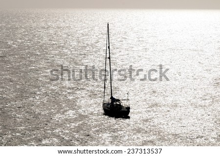 Silhouetted Sailing Boat on the Atlantic Ocean Near Canary Island - stock photo