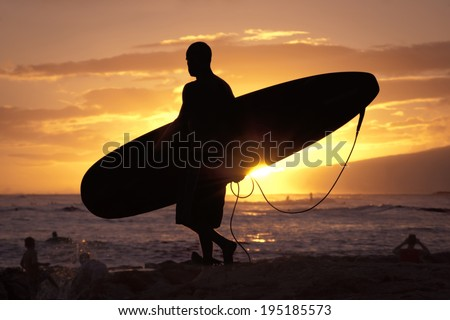 Silhouetted surfer at Waikiki Beach approaches the water at sunset. - stock photo