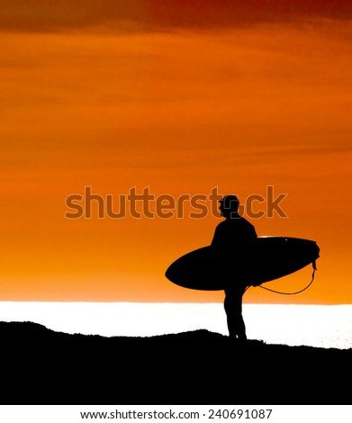 silhouetted Surfer walking out to sea to get the last wave in during sunset - stock photo