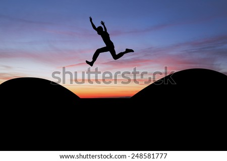 silhouetted teen jumping gap in sunset  - stock photo