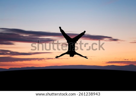 silhouetted young man jumping upside down in sunset  - stock photo