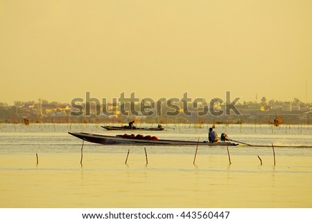silhouettes fishermen on boat in lake on morning time with sky sunrise background,select focus with shallow depth of field:ideal use for background. - stock photo
