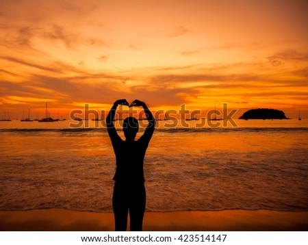 silhouettes love shape arm silhouette at sunset for background  - stock photo
