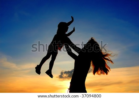 Silhouettes mother and child on sundown - stock photo