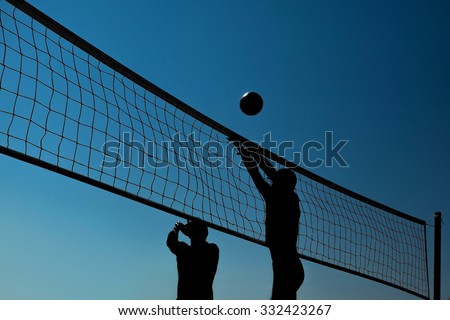 Silhouettes of a group of young people playing beach volleyball on the beach - stock photo