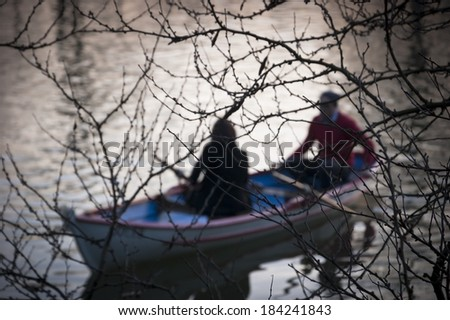 Silhouettes of  a man and woman in the boat on the lake. Twilight. Romance background. Harmony with nature idea.  - stock photo