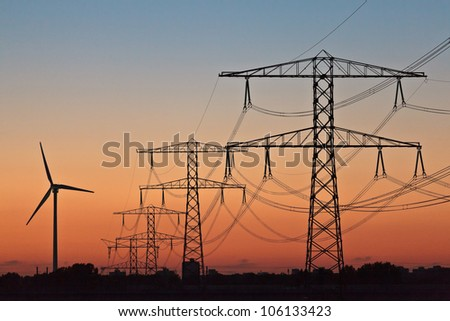 Silhouettes of a wind turbine and electric power posts during sunset - stock photo