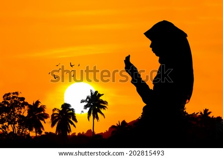 silhouettes of a women praying during sunset - stock photo