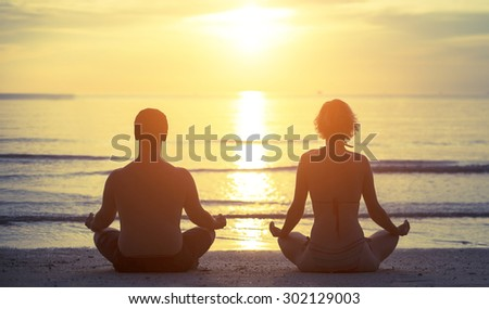 Silhouettes of a young couple sitting in the yoga Lotus position on the banks of the sea during sunset. - stock photo