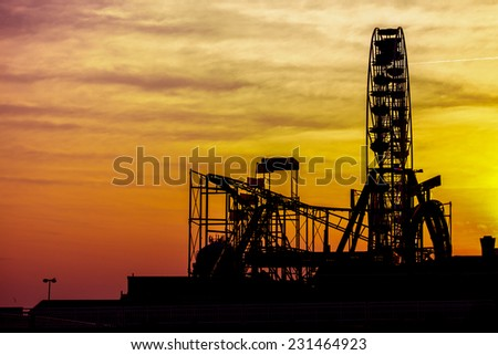 Silhouettes of amusement park at sunset - stock photo