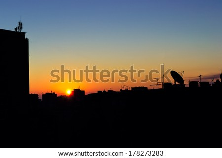Silhouettes of buildings, roofs and TV antennas at sunrise - stock photo