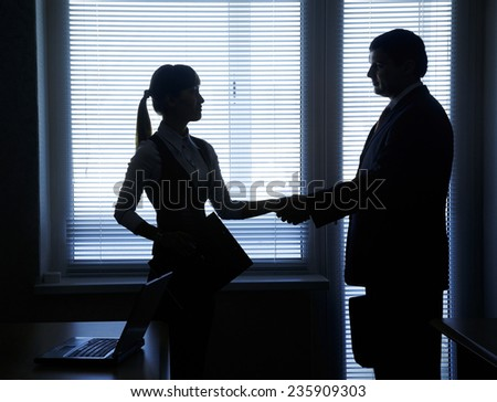 silhouettes of business partners handshake against the window in the office - stock photo