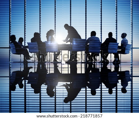 Silhouettes of business people in a conference room. - stock photo