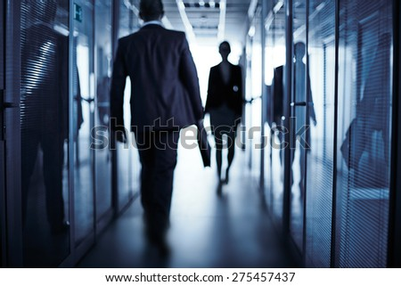 Silhouettes of business people walking along corridor of office building - stock photo