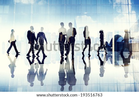 Silhouettes of Business People Walking inside the Office - stock photo