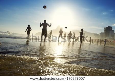 Silhouettes of carioca Brazilians playing sunset altinho futebol beach football soccer on the shore of Ipanema Beach Rio de Janeiro - stock photo
