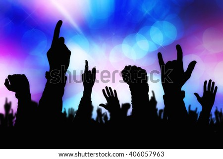 Silhouettes of concert crowd hands supporting band performing live music on stage, young people on rock gig enjoying. - stock photo
