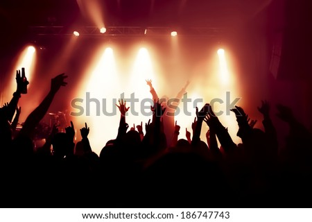 silhouettes of concert crowd in front of bright stage lights, singer on stage - stock photo