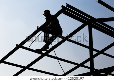 silhouettes of construction worker making structural steel roof - stock photo