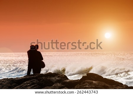 Silhouettes of couple in love standing and looking at waving ocean.Copy space, unrecognizable people, sunset light, lens flare - stock photo