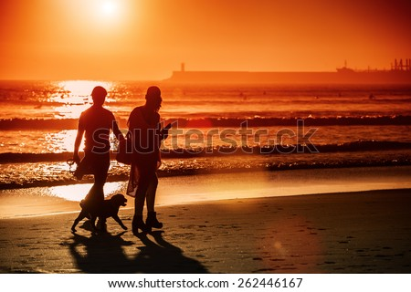 Silhouettes of couple walking dog at sunset beach, lens flare.Copy space, sunset light.Unrecognizable people - stock photo