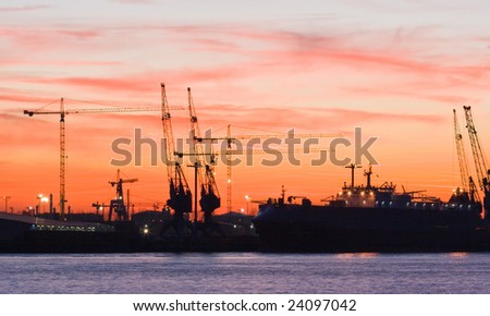 Silhouettes of cranes in the harbour by evening light - stock photo