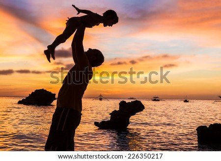 silhouettes of father and child on sunset sea background - stock photo
