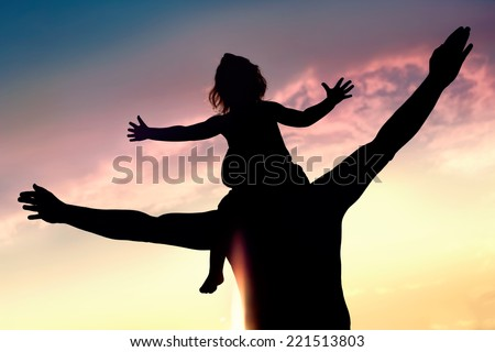 Silhouettes of father and daughter on his shoulders with hands up having fun, against sunset sky. Parenthood, family activities, beach holiday and vacation, support and love themes - stock photo