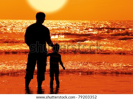 silhouettes of father and son on sunset - stock photo