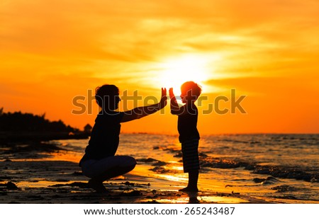 silhouettes of father and son playing at sunset sea - stock photo