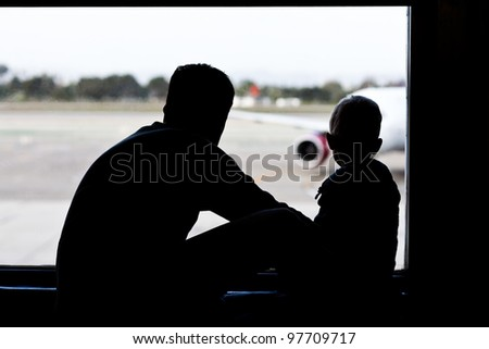 silhouettes of father and son watching the plane - stock photo