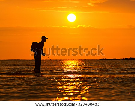 Silhouettes of fishermen on the beach with sunset moments. - stock photo
