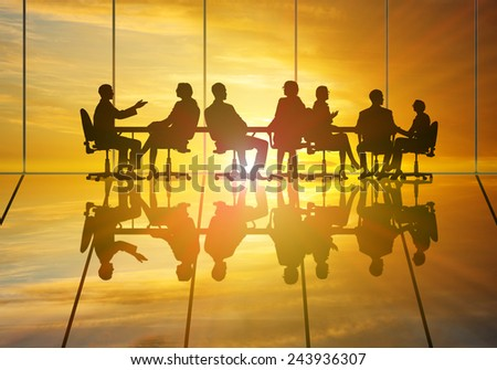 Silhouettes of group of business people against sunset - stock photo