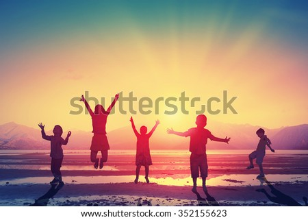 Silhouettes of group of children jumping high joyfully on sunset background - stock photo