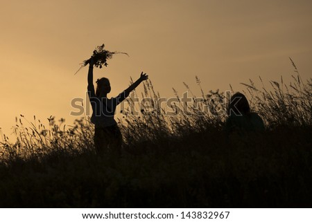 Silhouettes of happy girl picking flowers during midsummer soltice celebraton against the background of sunset - stock photo
