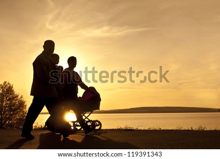 Silhouettes of happy parents - husband wife grandfather grandmother walking with stroller on the seacoast - stock photo